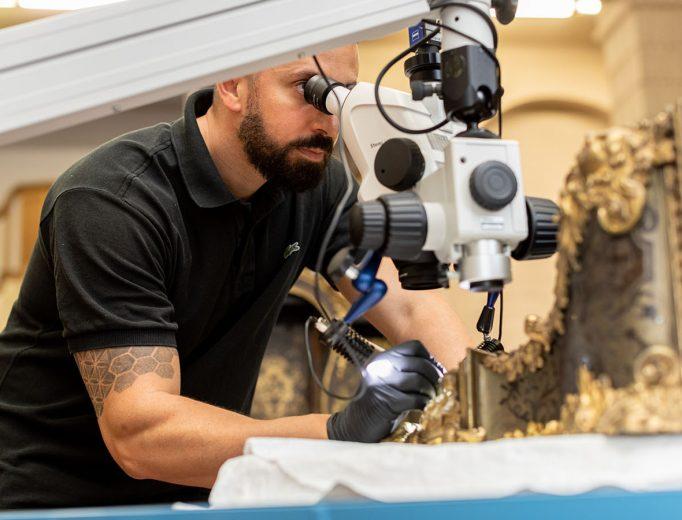Restaurator Lucas Nierhaus untersucht die Marketerie einer Konsole<br>Foto: David Pinzer<br>© Kunstgewerbemuseum, SKD